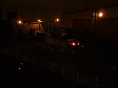 Stoneybridge West Yard by night. Working yard lighting using 'grain of rice' 3V lamps fed with 1.2V DC. Fire in hut 2 x bulbs with 'unstable flip-flop' circuit fire flicker effect.